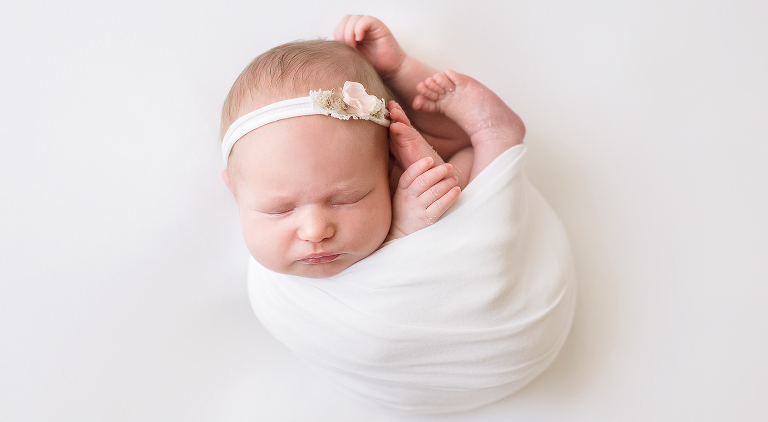 Newborn baby girl wrapped up in white with flower headband